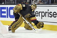 Vegas Golden Knights goaltender Marc-Andre Fleury (29) handles the puck behind the net against the Minnesota Wild during the third period of Game 1 of a first-round NHL hockey playoff series Sunday, May 16, 2021, in Las Vegas. (AP Photo/David Becker)