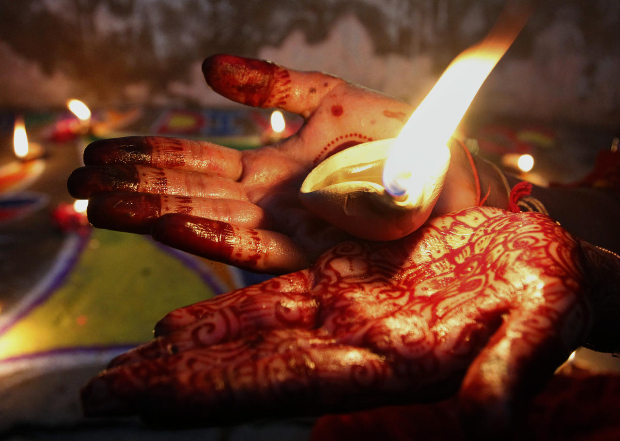 A Pakistani Hindu girl holds an earthen lamp while decorating an area of her house to celebrate Diwali, the Hindu festival of lights, Tuesday, Nov. 13, 2012 in Karachi, Pakistan. Hindus across the country are celebrating Diwali, where people decorate their homes with light and set off firecrackers. (AP Photo/Shakil Adil)
