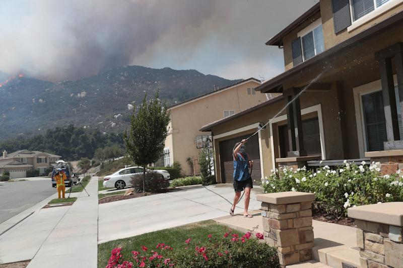 Stefanie Liesenfelt sprays her home with water at the Tenaja fire approaches in the Murrieta foothills near the end of Single Oak Way, September 5, 2019.