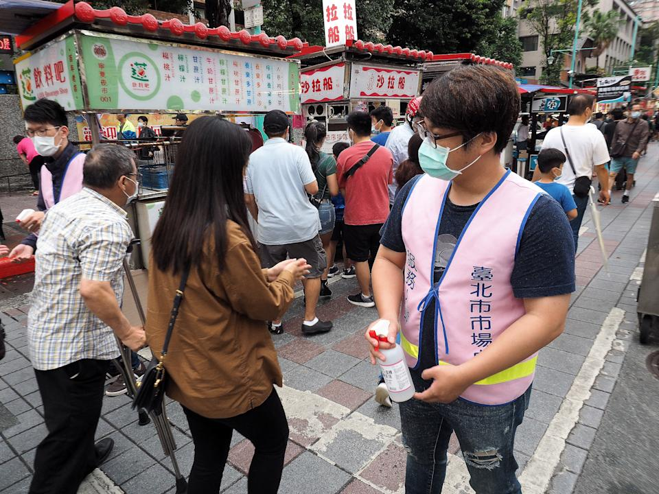 Two health workers stand ready to apply sanitising gel on people's hands at the Ningxia Night Market in Taipei, Taiwan, 22 May 2020. Source: EPA via AAP