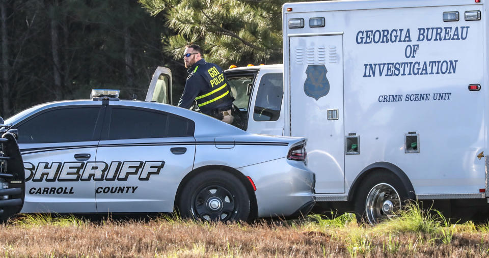 An officer with the Georgia Bureau of Investigation works at the scene following a police chase Monday, April 12, 2021, in Carroll County, Ga. Georgia authorities say multiple officers were injured when the passenger of a car shot them during a police chase that ended with one suspect killed and the other arrested. (John Spink/Atlanta Journal-Constitution via AP)