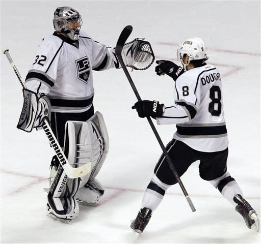 Los Angeles Kings goalie Jonathan Quick (32) celebrates with Drew Doughty (8) after the Kings defeated the Chicago Blackhawks 2-0 in an NHL hockey game in Chicago on Wednesday, Dec. 28, 2011. (AP Photo/Nam Y. Huh)