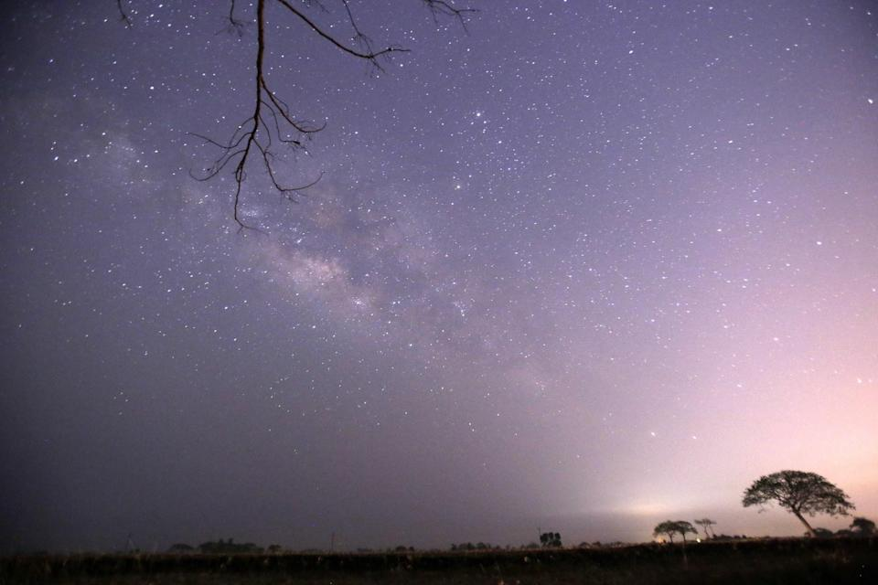 This long-exposure photograph taken on April 23, 2015 on Earth Day shows Lyrids meteors shower passing near the Milky Way in the clear night sky of Thanlyin, nearly 14miles away from Yangon (Ye Aung Thu/AFP/Getty Images)