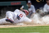 Philadelphia Phillies' Jean Segura (2) is out at home after Washington Nationals catcher Tres Barrera made a tag during the first inning of a baseball game, Monday, July 26, 2021, in Philadelphia. (AP Photo/Laurence Kesterson)