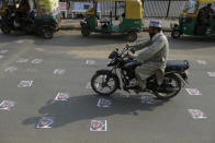 An Indian commuter moves on defaced images of French President Emmanuel Macron pasted by protestors on a road in Ahmedabad, India, Sunday, Nov. 1, 2020. Muslims have been calling for both protests and a boycott of French goods in response to France's stance on caricatures of Islam's most revered prophet. (AP Photo/Ajit Solanki)