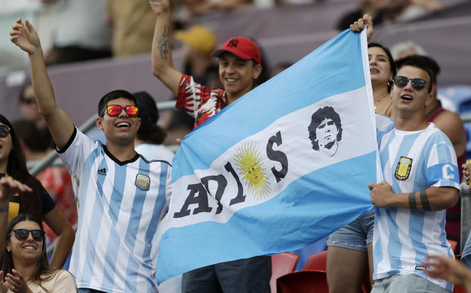Argentina fans hold a flag in memory of soccer star Diego Maradona ahead of the Tri-Nations rugby test between Argentina and the All Blacks in Newcastle, Australia, Saturday, Nov. 28, 2020. (AP Photo/Rick Rycroft)