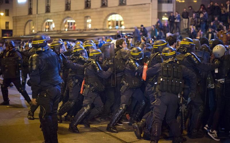 Anti riot police officers push a group of demonstrators during scufflings in Paris - AP