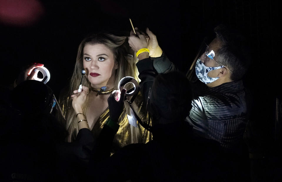 Masked crew members style host Kelly Clarkson during a commercial break at the Billboard Music Awards, Wednesday, Oct. 14, 2020, at the Dolby Theatre in Los Angeles. (AP Photo/Chris Pizzello)