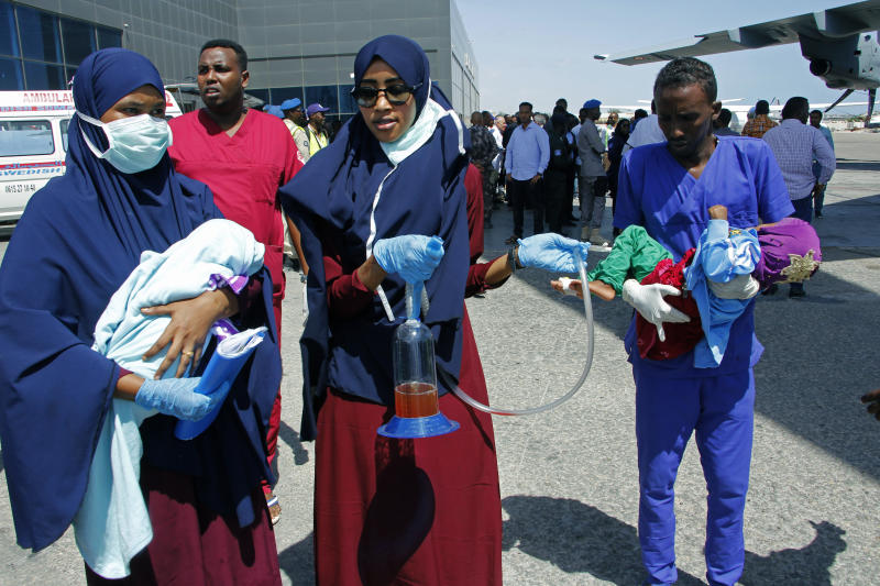 Medical personnel carry wounded children to be airlifted to the Turkish capital for treatment after they were injured in Saturday's car bomb blast in Mogadishu, Somalia, Sunday, Dec. 29, 2019.  A truck bomb exploded at a busy security checkpoint in Somalia's capital Saturday morning, killing at least 79 people including many students, authorities said. It was the worst attack in Mogadishu since the devastating 2017 bombing that killed hundreds. (AP Photo/Farah Abdi Warsameh)