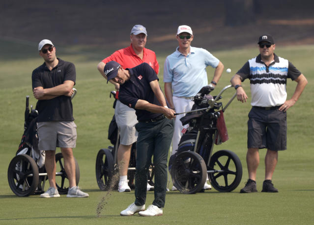 Australia's Adam Scott, center, hits his second shot on the 12th hole during the Australian Open Golf Pro-AM in Sydney, Wednesday, Dec. 4, 2019. The Australian Open begins Thursday. (AP Photo/Rick Rycroft)