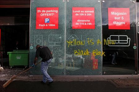 A man sweeps outside a vandalized store the morning after clashes with protesters wearing yellow vests, a symbol of a French drivers' protest against higher diesel fuel taxes, in Paris, France, December 2, 2018.  REUTERS/Stephane Mahe