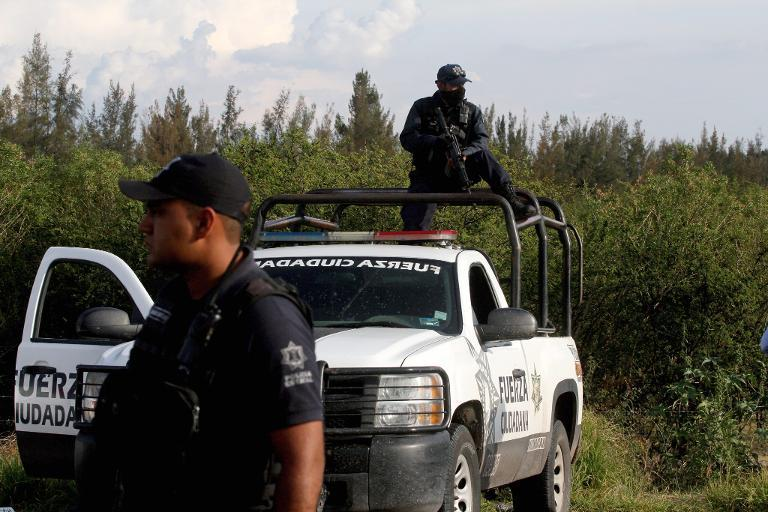 State policemen stand guard at the entrance of the ranch where gunmen took cover during an intense gun battle with the police, along the Jalisco-Michoacan highway in Vista Hermosa, Michoacan State on May 22, 2015