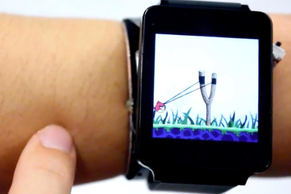 """<p>If you're a smartwatch owner, you're probably well aware of their pitfalls. While they're getting better, they still rely too much on a tiny display in order to function. And while manufacturers <em>could</em> make smartwatch displays larger, that would lead to some very unfashionable devices. The solution? Turn your whole forearm into an interface.</p> <p>That's the idea behind Future Interfaces Group's latest technology, called SkinTrack. With SkinTrack, a smartwatch includes a number of sensors, enabling it to treat your arm like a touch interface. Future Interfaces Group is a research lab based at Carnegie Mellon University.</p> <p><strong>Related: </strong><a href=""""http://www.digitaltrends.com/wearables/huawei-watch-elegant-jewel/"""" rel=""""nofollow noopener"""" target=""""_blank"""" data-ylk=""""slk:Put some bling on it: Huawei's Swarovski studded smartwatches are now on sale"""" class=""""link rapid-noclick-resp"""">Put some bling on it: Huawei's Swarovski studded smartwatches are now on sale</a></p> <p>The system basically works with a ring that's worn on the finger and communicates with a sensor on the smartwatch. When the finger wearing the ring touches the skin near the watch, an electrical signal is sent through the arm. The watch is able to triangulate the location of the finger using the distance between the ring and a total of four sensors in the band of the watch.</p> <p>There's a ton of cool stuff you can do when you have your whole arm to interface with. Take a look at the video, and you'll see apps being dragged onto your skin, which you can then tap on to return to the app. You can even use your arm to pull the slingshot further back in <em>Angry Birds</em>!</p> <p>The system could also greatly expand the number of shortcuts available in a smartwatch — for example, we can see the user silencing a phone call simply by dragging out the letter 'S' on their skin. SkinTrack can even track your finger when it's hovering above the skin.</p> <p>""""The great thing about SkinTrac"""