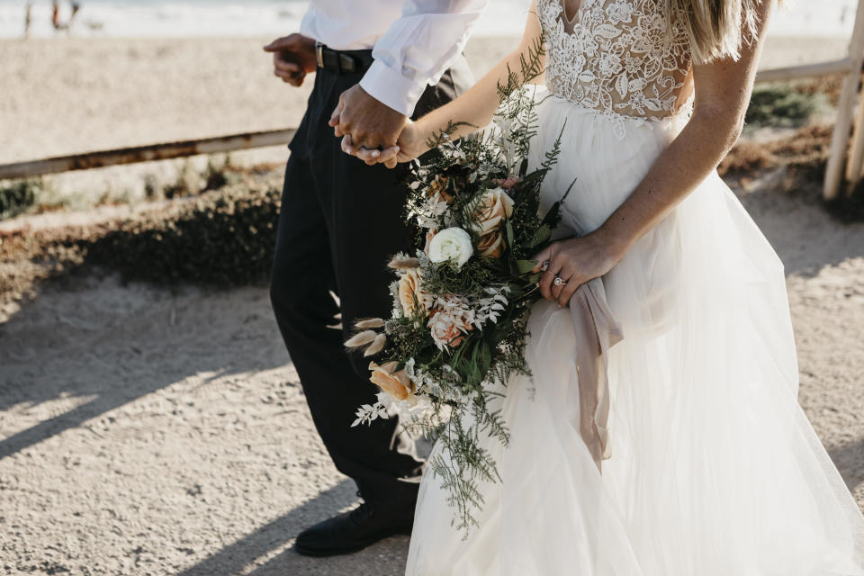 Close-up of bride and groom walking on path at the coast