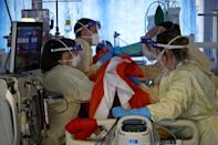 Joslin, second-left, and fellow firefighter Tom Ventress work with critical care nurses to roll a patient onto their front