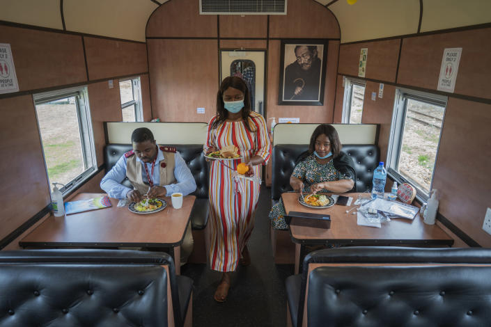 From left, Sibonino Nene, head of vaccination program, Ntombekhaya Kondile, data capturer, and Transvaco Manager Dr. Paballo Mowana have lunch aboard the COVID-19 vaccination train parked at the Swartkops railroad yard outside Gqeberha, South Africa, Thursday Sept. 23, 2021. South Africa has sent a train carrying COVID-19 vaccines into one of its poorest provinces to get doses to areas where healthcare facilities are stretched. The vaccine train, named Transvaco, will go on a three-month tour through the Eastern Cape province and stop at seven stations for two weeks at a time to vaccinate people. (AP Photo/Jerome Delay)