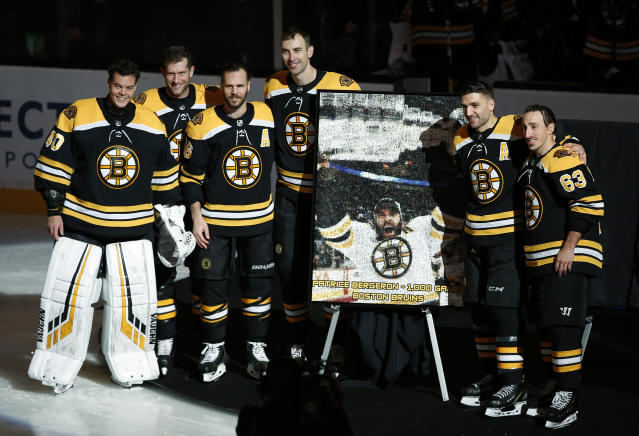Boston Bruins' Patrice Bergeron, second from right, stands with teammates from left, Tuukka Rask, David Backes, David Krejci, Zdeno Chara and Brad Marchand during a ceremony honoring Bergeron for playing in his 1,000 career game before an NHL hockey game between the Boston Bruins and the Los Angeles Kings, Saturday, Feb. 9, 2019, in Boston. (AP Photo/Winslow Townson)