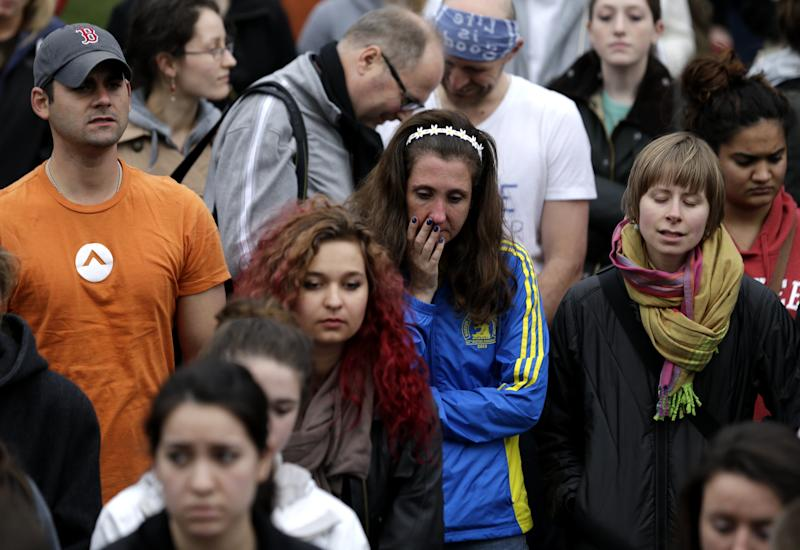 A woman wearing a Boston Marathon jacket, center, attends a vigil for the victims of the Boston Marathon explosions at Boston Common, Tuesday, April 16, 2013, one day after bombs exploded at the finish line of the Boston Marathon. (AP Photo/Julio Cortez)