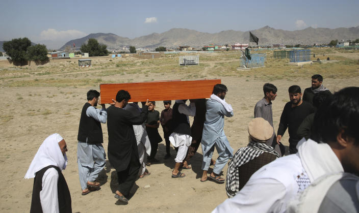 Afghans carry the body of a victim of Dubai City wedding hall bombing during a mass funeral in Kabul, Afghanistan, Sunday, Aug.18, 2019. The deadly bombing at the wedding in Afghanistan's capital late Saturday that killed dozens of people was a stark reminder that the war-weary country faces daily threats not only from the long-established Taliban but also from a brutal local affiliate of the Islamic State group, which claimed responsibility for the attack. (AP Photo/Rafiq Maqbool)