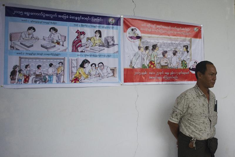 A man stands next to election posters at the Zabuthiri district election commission office in Naypyidaw on August 14, 2015 (AFP Photo/Ye Aung Thu)