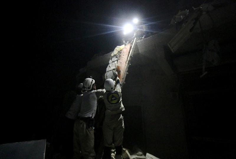 Syrian members of the emergency services personnel carry a body on a stretcher over rubble after a missile fired by Syrian government forces hit a residential area in Aleppo on August 2, 2015