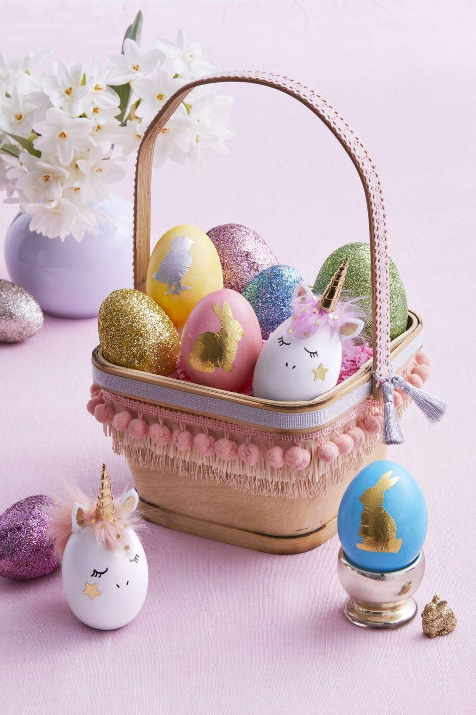 """<p>Make a plain square basket look magical with a few scraps of ribbon and trim, and fill with unicorn-inspired and sparkling Easter eggs.</p><p><strong>Lovely Unicorn:</strong> Paint a wooden egg white; let dry. Draw on face. Cut a mane from faux-fur trim, color in an egg dye bath, and attach (once dry) with fabric glue. Use templates to make felt ears and a gold paper horn; assemble and glue to egg. Wrap a 3 x 1/8-in. strip of gold paper around horn; secure with glue. Glue star confetti to cheek and hair.</p><p><strong>Shiny Silhouette:</strong> Use the templates to carefully cut a chick or bunny from a foil candy wrapper. Adhere to dyed egg with Mod Podge. Use a damp cotton swab to gently wipe clean the foil shape; let dry.</p><p><strong>Dazzling Glitter Egg:</strong> Try this trick on basic plastic eggs: Lightly sand the outside, brush on glue, cover in glitter, and let dry.</p><p><strong><em><a href=""""https://www.womansday.com/home/crafts-projects/a18837631/easter-egg-templates/"""" rel=""""nofollow noopener"""" target=""""_blank"""" data-ylk=""""slk:Get the templates here."""" class=""""link rapid-noclick-resp"""">Get the templates here.</a></em></strong></p><p><strong><a class=""""link rapid-noclick-resp"""" href=""""https://www.amazon.com/Supplies-Resistant-Polyester-Eyeshadow-Assorted/dp/B076J9RD8P/?tag=syn-yahoo-20&ascsubtag=%5Bartid%7C10070.g.1751%5Bsrc%7Cyahoo-us"""" rel=""""nofollow noopener"""" target=""""_blank"""" data-ylk=""""slk:SHOP GLITTER"""">SHOP GLITTER</a></strong></p>"""