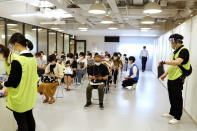 Medical workers wait to get Moderna's COVID-19 vaccine at an inoculation site set up by Japanese technology company SoftBank Group Corp. at a WeWork office Tuesday, June 15, 2021, in Tokyo. Japanese companies have joined the effort to speed up the country's lagging coronavirus vaccine rollout before the Tokyo Olympics begin next month. (AP Photo/Yuri Kageyama)