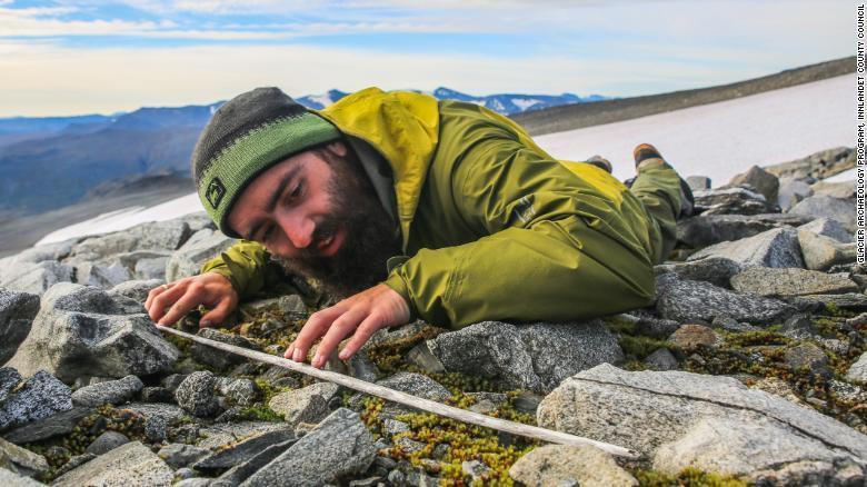 <p>An archaeologist surveys a glacier in Norway</p> (Glacier Archaeology Programme, Innlandet County Council)