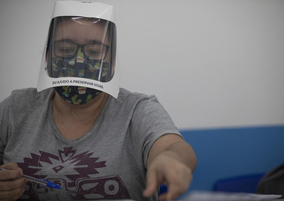 """An electoral worker wears a face shield with a sign that reads """"I help to preserve lives"""" during municipal elections at a polling station in the Rocinha slum in Rio de Janeiro, Brazil, Sunday, Nov. 15, 2020. (AP Photo/Silvia Izquierdo)"""