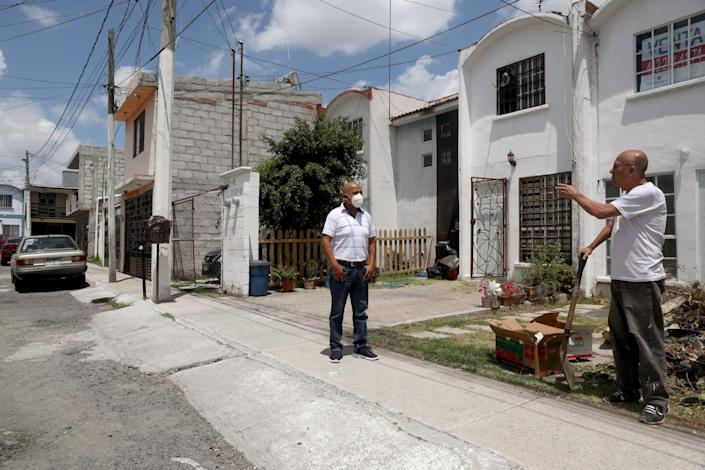 "Fernando Trejo Reyes talks with a neighbor in Querétaro. ""I never knew what unemployment was,"" he says. <span class=""copyright"">(Gary Coronado / Los Angeles Times)</span>"