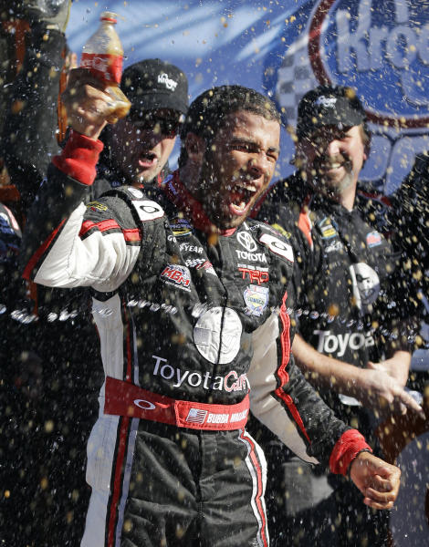 Driver Darrell Wallace Jr. celebrates in Victory Lane winning the NASCAR Truck Series auto race at Martinsville Speedway in Martinsville, Va., Saturday, Oct. 26, 2013. (AP Photo/Steve Helber)