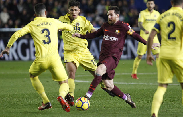 Barcelona's Lionel Messi , center, duels for the ball with Villarreal's Alvaro Gonzalez , left, during the Spanish La Liga soccer match between Villarreal and FC Barcelona at the Ceramica stadium in Villarreal, Spain, Sunday, Dec. 10, 2017. (AP Photo/Alberto Saiz)