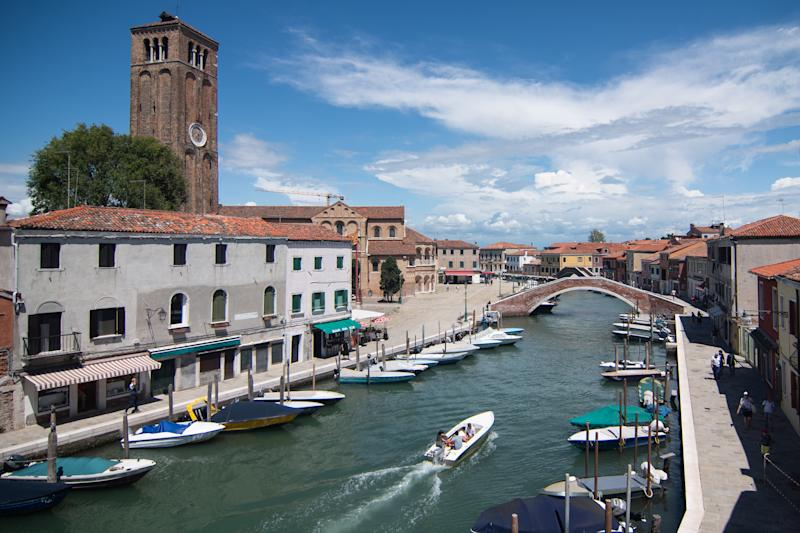 VENICE, ITALY - JULY 17: A boat cruises on an empty canal of the island of Murano on July 17, 2020 in Venice, Italy. After the lockdown for the Covid-19, the tourism in the island of Murano is at a very low level, and a lot activities are suffering and near to the closure. (Photo by Simone Padovani/Awakening/Getty Images)