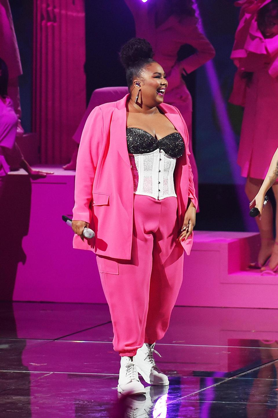 Speaking of corsets and pink. Lizzo's stage outfits have just as much presence as her music. At <em>The Voice of Italy</em>, she sported a hot pink power suit and her all-time favorite white Dr. Martens.