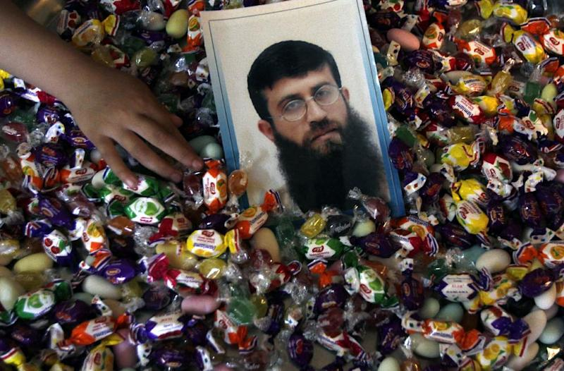 A photograph of Islamic Jihad member Khader Adnan jailed in Israel, placed on a basket of sweets Monday, April. 16, 2012 ahead of his release Tuesday from prison in the the West Bank village of Arrabeh near Jenin. Adnan will be released after he had a 66-day hunger strike to protest his imprisonment without charge. (AP Photo/Mohammed Ballas)