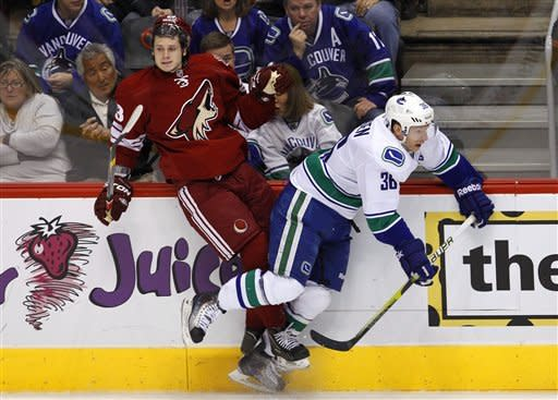 Vancouver Canucks' Jannik Hansen (36), of Denmark, checks Phoenix Coyotes' Oliver Ekman-Larsson, of Sweden, into the boards during the first period in an NHL hockey game, Tuesday, Feb. 28, 2012, in Glendale, Ariz. (AP Photo/Ross D. Franklin)
