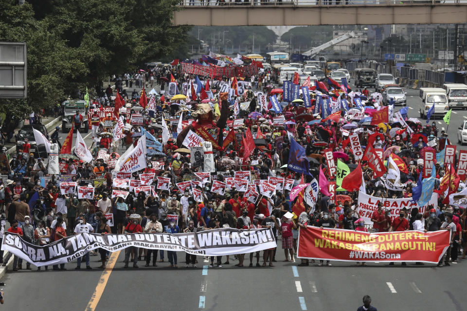 Protesters march towards the House of Representatives where Philippine President Rodrigo Duterte is set to deliver his final State of the Nation Address in Quezon city on Monday, July 26, 2021. Duterte is winding down his six-year term amid a raging pandemic and a battered economy. (AP Photo/Gerard Carreon)