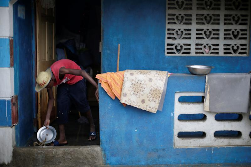 A man uses a metal plate to remove water from his house in Fort Liberte, Haiti