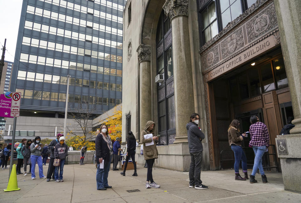 People wait in line to apply for mail-in or absentee ballots at the County Office Building Tuesday, Oct. 27, 2020, in Pittsburgh. (Steve Mellon/Pittsburgh Post-Gazette via AP)