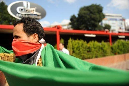 A man wears a Libyan flag over his mouth during a demonstration against Moamer Kadhafi in Istanbul. Western and regional powers have boosted Libyan rebels battling Moamer Kadhafi by designating them as the country's legitimate rulers, a move that gives them access to vital funds