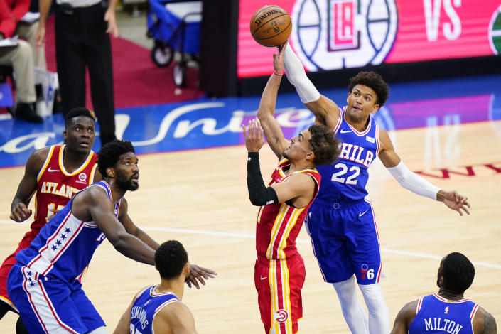 Atlanta Hawks' Trae Young, center, goes up for a shot past Philadelphia 76ers' Matisse Thybulle, right, during the second half of Game 2 in a second-round NBA basketball playoff series, Tuesday, June 8, 2021, in Philadelphia. (AP Photo/Matt Slocum)