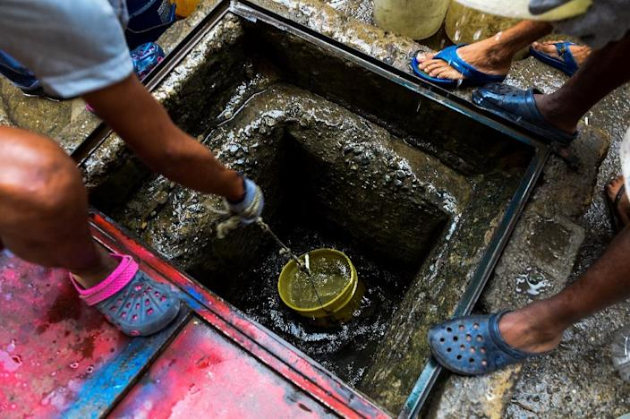 People draw water from a spring water tank to be used in their toilets in Caracas (AFP Photo/Federico Parra)