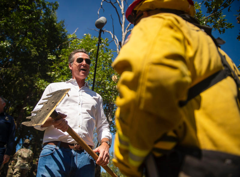 Gov. Gavin Newsom holds a Mcleod, a tool that helps with vegetation pruning and minimizes fire risk, while talking to a member of Cal Fire on Wagon Trail in the Sierra Foothills in Colfax, Calif. Wednesday, July 31, 2019. (Daniel Kim/The Sacramento Bee via AP, Pool)