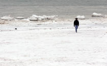 A man walks next to the snow-covered Lake Michigan in Evanston, Ill., Friday, Jan. 3, 2014. The snowstorm may finally have left town but a winter weather advisory is in effect for this evening when southerly winds are expected to kick up blizzard-like conditions. (AP Photo/Nam Y. Huh)