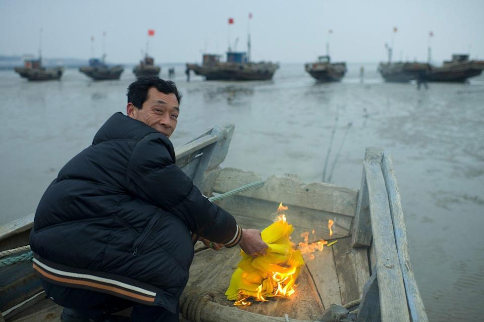 A Chinese fisherman burns joss papers to sacrifice on his fishing boat during the ceremony of sacrifice to the sea God in Zhougezhuang village. Photo: Getty