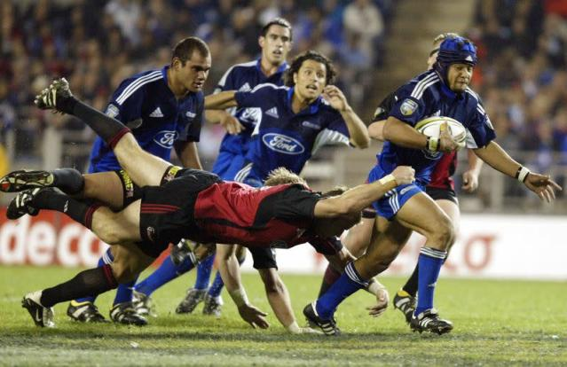 FILE PHOTO: BLUES TUITUPOU TRIES TO EVADE CRUSADERS TACKLE DURING FINAL OF SUPER 12 IN AUCKLAND