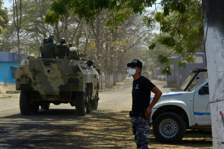 Soldiers are seen on an armoured vehicle outside a prison in Guayaquil, Ecuador where a bloody prison riot left more than 100 inmates dead (AFP/Fernando Mendez)
