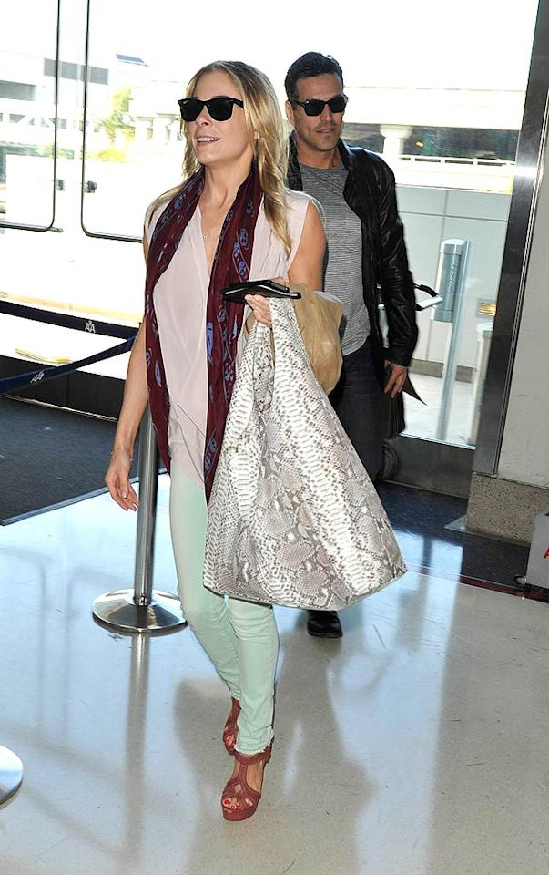"LeAnn Rimes and her fiance Eddie Cibrian arrived at LAX to catch a flight on Monday. Of course, the country music star opted to sport a pair of high Miu Miu platform sandals instead of sensible traveling shoes! Hot Shots Worldwide/<a href=""http://www.splashnewsonline.com"" target=""new"">Splash News</a> - March 28, 2011"