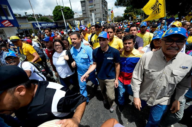 Venezuelan opposition leader Henrique Capriles (C, with cap) marches to demand electoral power to activate the recall referendum against President Nicolas Maduro, in Caracas on July 27, 2016 (AFP Photo/Federico Parra)