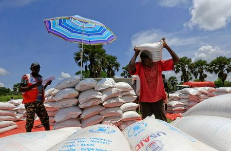 FILE PHOTO: Refugees from South Sudan offload food items from the World Food Program (WFP) trucks in Palorinya settlement camp for distribution in Moyo district northern Uganda October 26, 2017. REUTERS/James Akena/File Photo